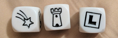 three dice showing a shooting star, a castle tower, and the letter L in a box